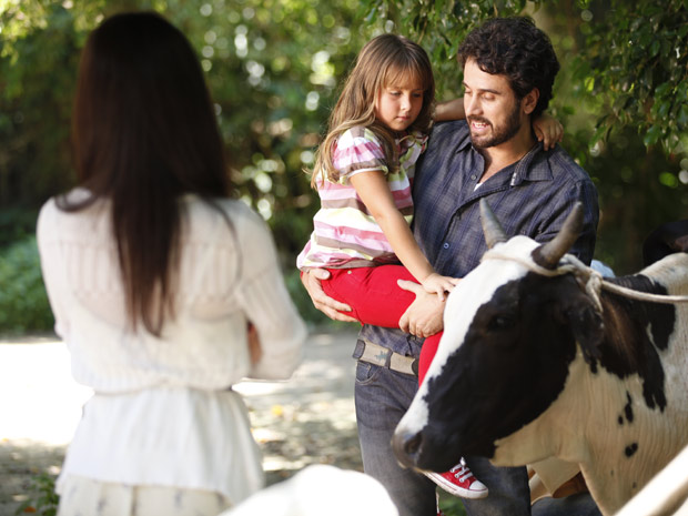 Com jeitinho, Gabriel convence Júlia a chegar perto da vaquinha, e Manu observa admirada (Foto: A Vida da Gente / TV Globo)