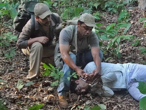 Caçadores encontram o rapaz caído no chão, e encontram o número do telefone de Patrícia (Foto: Fina Estampa/TV Globo)