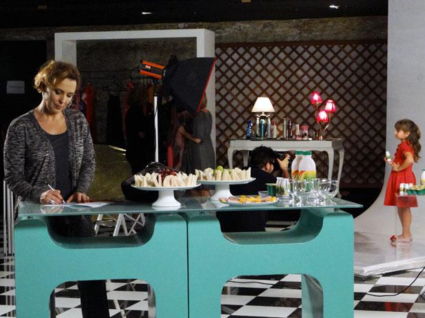 Enquanto Júlia faz as fotos, Eva falsifica a assinatura de Ana na autorização (Foto: A Vida da Gente / TV Globo)