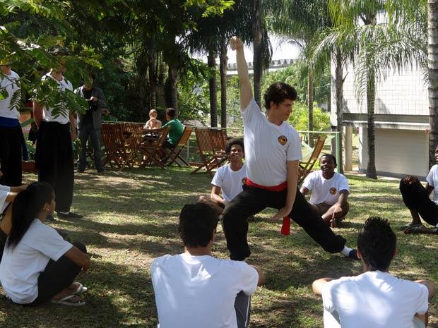 Gabriel está dando aula de kung fu na praça para meninos da comunidade e é observado por um diretor de cinema