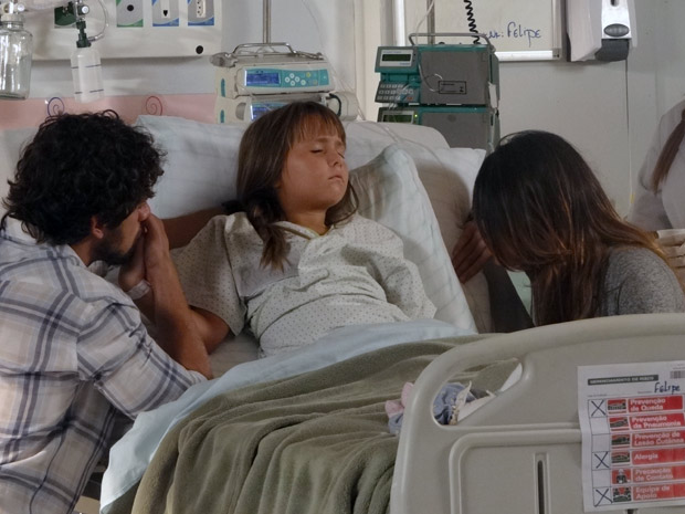 Júlia dorme sob efeito do medicamento, e Ana e Rodrigo seguram as mãos da menina (Foto: A Vida da Gente / TV Globo)