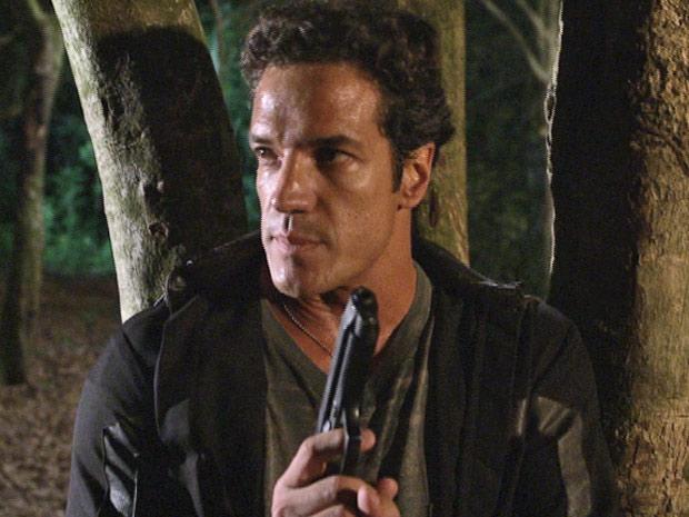 Ferdinand se esconde da polícia atrás de uma árvore (Foto: Fina Estampa/TV Globo)