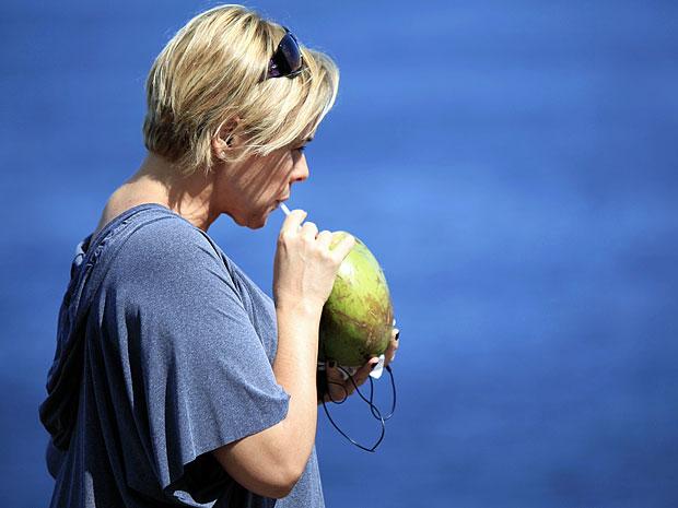 Giulia Gam toma água de coco em cena (Foto: Amor Eterno Amor/TV Globo)
