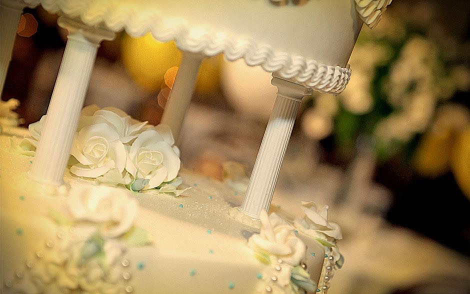 O bolo é todo decorado com detalhes em flores brancas e bolinhas azuis