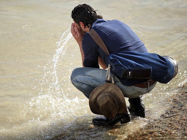 Carlos molha o rosto com a água do mar (Foto: Amor Eterno Amor/TV Globo)