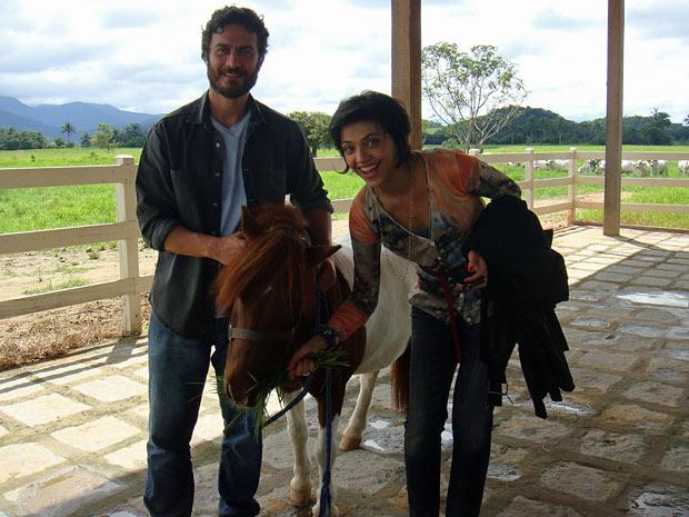 Gabriel Braga Nunes e Letícia Persiles brincam e alimentam o pônei (Foto: Amor Eterno Amor/TV Globo)