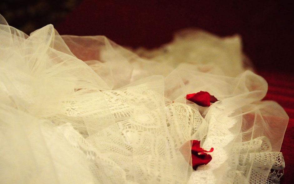 Pétalas de rosa sobre a cauda do vestido e o véu de Claudia