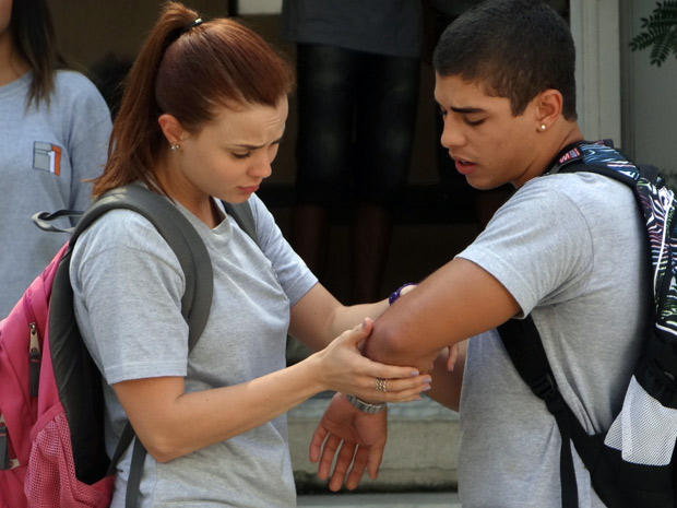 Débora fica preocupada com o namorado e examina o braço do rapaz (Foto: Malhação / Tv Globo)