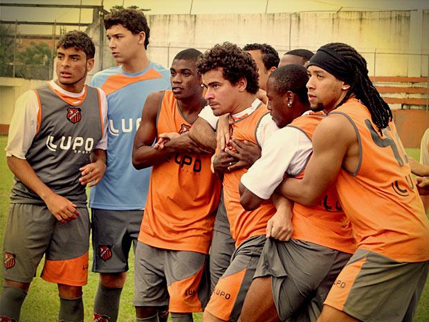 Leandro é contido pelos colegas do Divino (Foto: Avenida Brasil/ TV Globo)