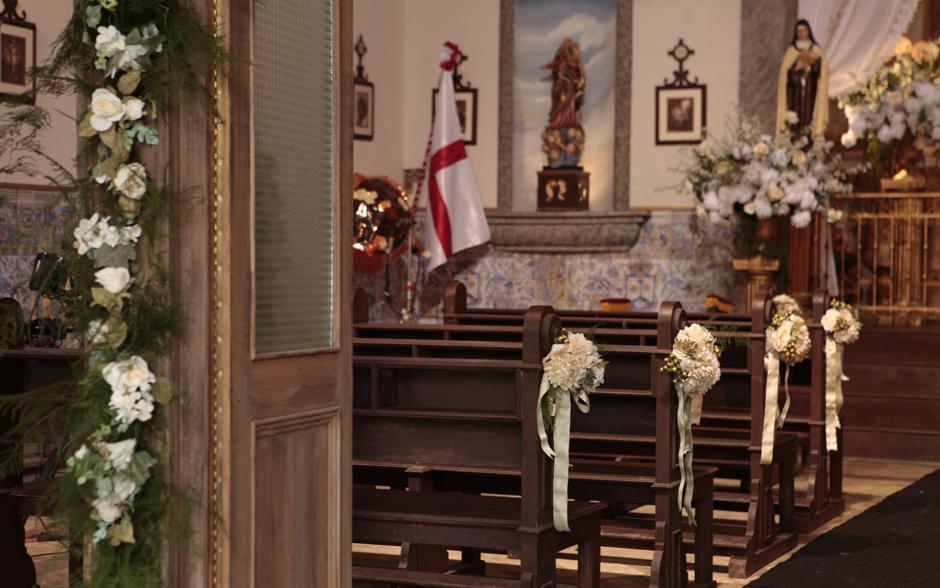 No caminho da noiva até o altar estão os tradicionais arranjos de flores brancas