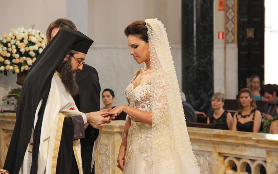 O padre coloca a aliança abençoada no dedo de Drika