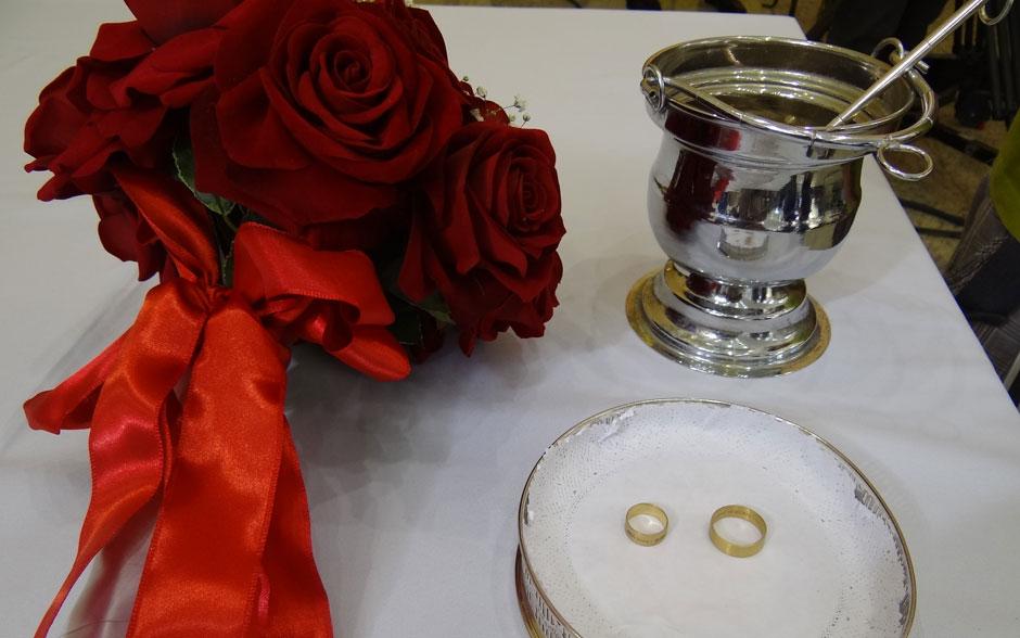 Buquê de rosas vermelhas e as alianças dos noivos, com a frase 'te amo' em várias línguas