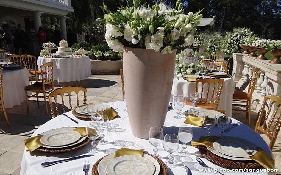Os arranjos da mesa eram diferentes entre si. Nesta, a opção foi por um vaso alto recheado de flores brancas
