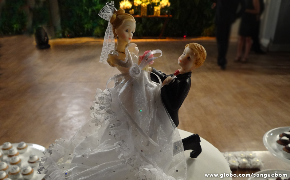 Detalhe do bonequinho todo apaixonado pela noiva em cima do bolo
