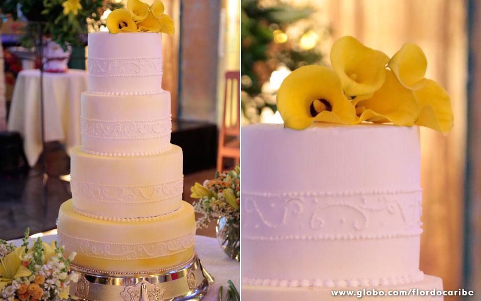 Com quatro andares, o bolo ganhou um degradê de amarelo. O enfeite no topo traz flores copo-de-leite na mesma cor