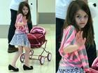 Suri Cruise empurra carrinho de bebê e acena para paparazzo