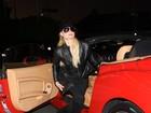 Toda de preto, Paris Hilton badala com sua Ferrari vermelha