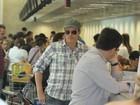 De boné e óculos escuros, Dalton Vigh embarca em aeroporto do Rio