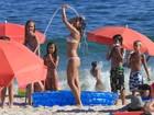 Com os filhos, Ana Lima toma banho de mangueira em praia no Rio