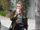 Miley Cyrus passeia de short curto e meia calça que imita cinta-liga