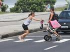 Dani Monteiro atravessa a rua correndo com a filha