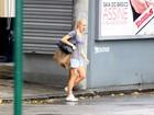 Na chuva, Fiorella Mattheis anda sozinha pela Gávea, no Rio