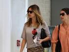 De calça de oncinha, Fernanda Lima  circula pelo aeroporto do Rio