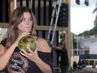 Tomando água de coco, Cristiana Oliveira posa em praça de Goiânia