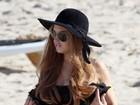 Lindsay Lohan fuma na praia e ganha massagem de uma amiga