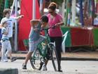 Em plena forma, ex-Globeleza ensina o filho a andar de bicicleta