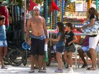 Sem camisa, Roger Flores passeia com crianças no Rio