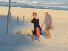 Christine Fernandes passeia em praia com cachorro