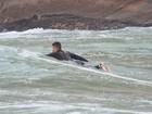 Mesmo com baixas temperaturas, Cauã Reymond surfa em praia do Rio