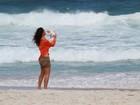 Débora Nascimento passeia com cachorrinho de lacinho em praia