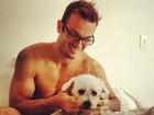 Diego Hypolito posa sem camisa na cama com cãozinho fofo