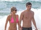 De biquíni rosa, Paris Hilton curte praia muito bem acompanhada