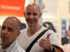 Sorridente, Tande embarca em aeroporto no Rio
