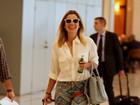 Sorridente, Flávia Alessandra embarca em aeroporto no Rio