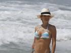 Flávia Alessandra grava novela de biquíni na praia e exibe corpão