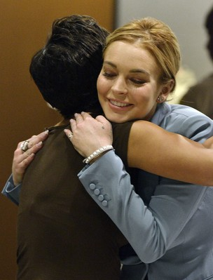 Lindsay Lohan abraça sua advogada no tribunal ao saber que conseguiu a condicional informal (Foto: AFP)