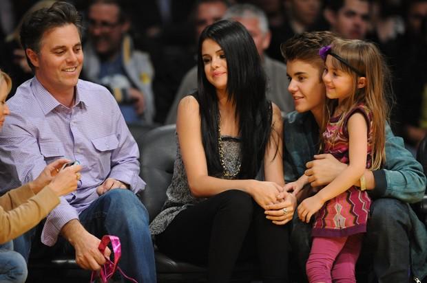 Justin Bieber e Selena Gomez abraçam fã-mirim em jogo de basquete (Foto: Getty Images)