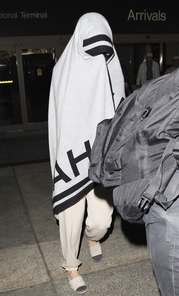 Katy Perry usa um cobertor para se esconder ao desembarcar no aeroporto de Los Angeles, nos Estados Unidos (Foto: X17/ Agência)