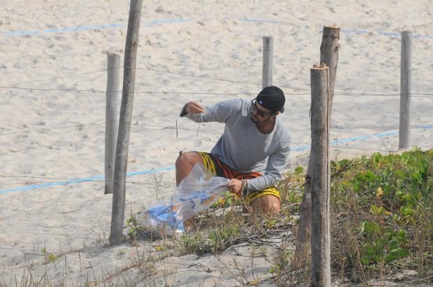 Paulo Vilhena catando lixo na praia do Recreio, no Rio (Foto: Francisco Silva / AgNews)