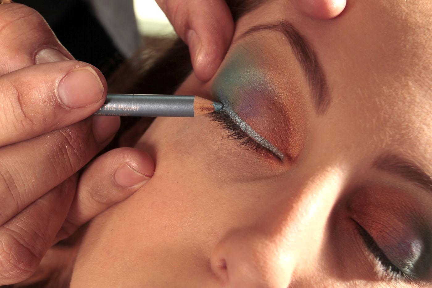 Passe um lápis de olho azul cintilante rente aos cílios para delinear, depois passe na parte inferior externa