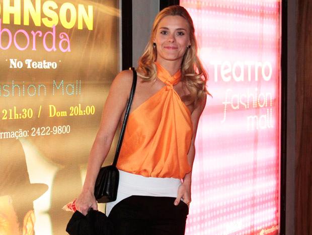 Carolina Dieckmann escolheu uma blusa laranja vibrante para assistir à estreia da peça do amigo Eri Johnson