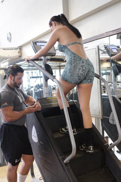 Flávia Piana começa seu treino com um exercício aeróbico, no qual simula a subida de escadas. Ela faz um minuto caminhando e dois subindo dois degraus, o que acaba virando trabalho de força para os glúteos também