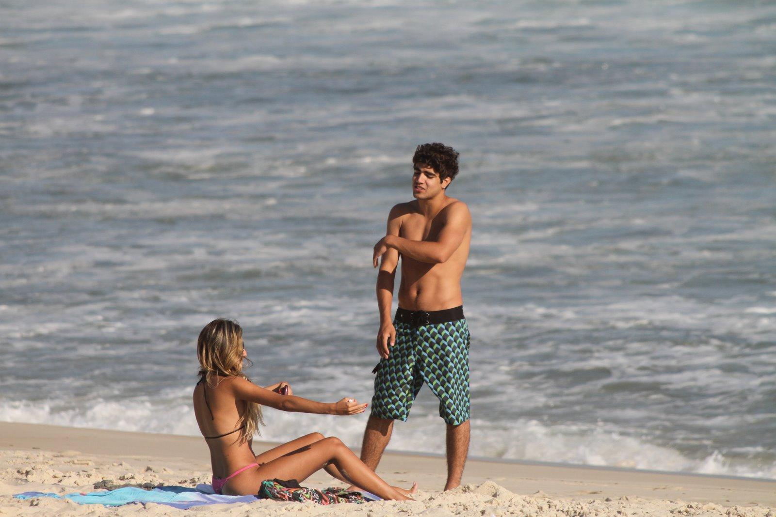 Caio Castro papeia com a sua companhia pela praia da Barra