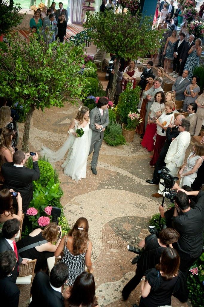 Os noivos são cercados pelos fotógrafos e pelos convidados do casamento