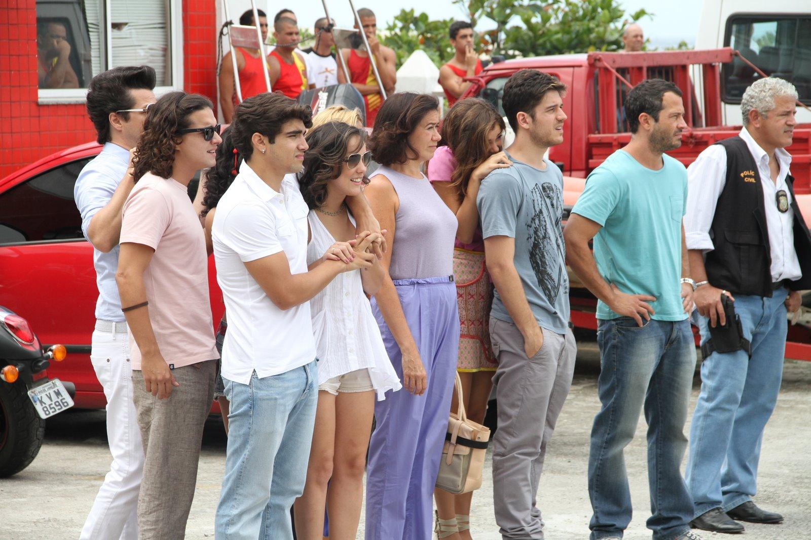Família Pereira, Crô, Solange e Daniel observam algo ao lado de policial: o que será?