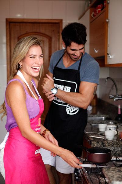 De avental, Adriana e Rodrigão se preparam para começar a cozinhar e se divertem